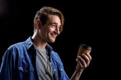 Optimistic guy is offering hot latte. Would you like some coffee. Positive young man is standing and holding cup of fresh espresso while expressing gladness Stock Photo