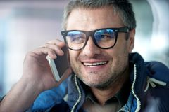 Optimistic guy is standing with mobile phone Stock Photography