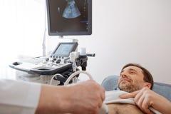 Optimistic guy undergoing ultrasound investigation Stock Photos