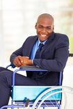 Optimistic handicapped businessman. Optimistic handicapped african businessman sitting on wheelchair Royalty Free Stock Photography