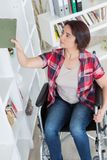Optimistic handicapped middle aged woman sitting on wheelchair stock photography