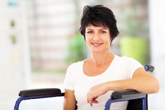 Optimistic handicapped woman. Optimistic handicapped middle aged woman sitting on wheelchair Royalty Free Stock Photo