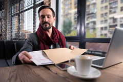 Optimistic handsome man putting a calendar into the envelope Royalty Free Stock Photography