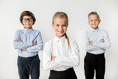 Optimistic intelligent kids are feeling gladness. Professional smart team concept. Portrait of cheerful cute kids are standing with crossed arms and looking at royalty free stock photo