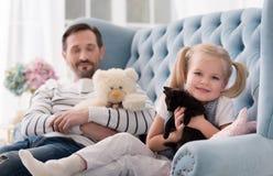 Optimistic joyful girl hugging her kitten Stock Photography