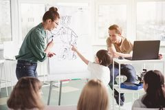 Optimistic kid talking with adults during lesson. What is it. Happy child pointing at image on board while telling about toy. Satisfied teachers listening him Royalty Free Stock Photos