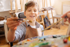 Optimistic little boy painting and mixing tones at school Stock Photo