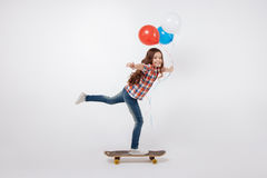 Optimistic little child skateboarding in the studio. Mastering new abilities . Gifted smiling graceful child expressing joy and holding colorful balloons while Stock Images