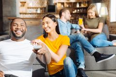 Optimistic loving couple watching comedy. Funny comedy.  Joyful sweet young  couple sitting next to each other while she placing hands on his shoulder and Stock Images