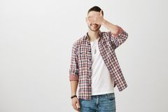 Optimistic male with bristly in checked shirt over t-shirt smiling brightly while covering eyes with palm, being. Confident and calm over gray background. Guy Royalty Free Stock Image