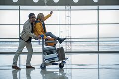 Optimistic male and female are walking to departure area. Joyful start of journey. Profile of happy young couple is having fun in terminal lounge. Man is pushing Royalty Free Stock Photo
