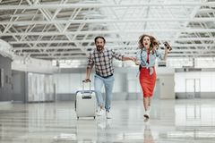 Optimistic male and girl running with baggage stock images