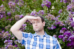 Optimistic man in front of purple flowers looking out hopeful for the future. Optimistic man in a plaid shirt looking out hopeful for the future with a bush Royalty Free Stock Images