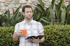 Optimistic man looking out with book and coffee mug in hand. Royalty Free Stock Image