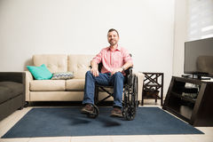Optimistic man on a wheelchair at home Stock Images