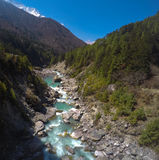 Optimistic nepalese view to mountain river valley with green forest and rocky riverbed Royalty Free Stock Photos