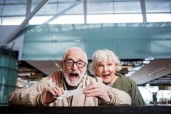 Optimistic old couple is expressing amaze. Feeling astonishment. Portrait of surprised gray-haired happy wife and husband are standing at airport while holding Stock Photo
