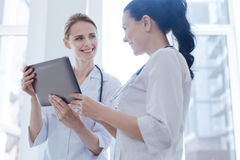 Optimistic oncologists using digital gadget at work Royalty Free Stock Images