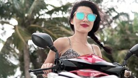 Optimistic pretty woman riding her motorbike stock video