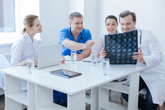 Optimistic radiologists discussing brain x ray image at the laboratory Stock Image