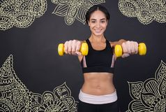 Optimistic sportswoman looking happy while holding hand weights Stock Images