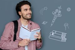 Optimistic student reading a book and thinking about other planets. Pleasant dream. Cheerful optimistic young man standing with a book in his hands and dreaming Royalty Free Stock Images