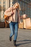 Optimistic stylish girl is evincing joy while carrying shopping bag stock photo