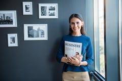 Optimistic stylish girl is posing with magazine Royalty Free Stock Image