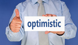 Optimistic. Text 'optimistic' in blue bold lower case text on a white card held by a businessman in blue shirt and silver tie with his thumb up for success, blue Royalty Free Stock Images