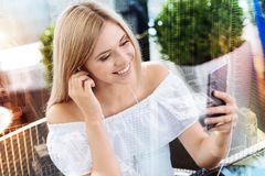 Optimistic thoughtful woman  relaxing with music. Music inspires. Creative positive young woman putting headphone in the ear while staring at the phone and Stock Images