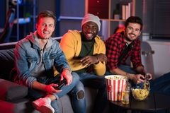 Optimistic trendy energy males are spending time together at home. Best friends. Portrait of cheerful stylish young guy is resting on couch with joystick while royalty free stock image
