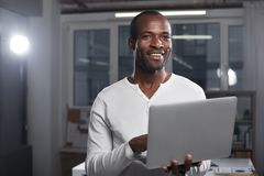 Optimistic trendy manager is feeling gladness. Enjoying modern technologies. Portrait of delighted positive young african businessman in casual clothes is royalty free stock photos