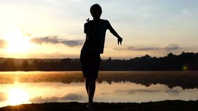 Cheery man dances rave on a lake bank at sunset