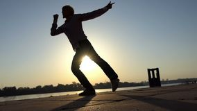 Jolly man dances actively on a river bank in summer in slo-mo. An optimistic view of a young slim man who dances actively on a river bank at a wonderful sunset stock footage