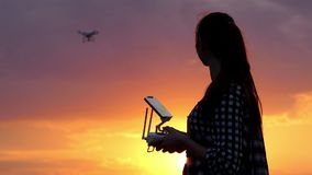 Smiling woman operates a panel to control a drone at sunset. An optimistic view of a young woman who smiles and operates a panel with a screen to control a stock video
