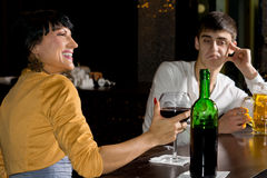 Optimistic woman drinking red wine at the bar. Optimistic young brunette women drinking red wine at the bar next to her pessimistic male friend drinking beer Royalty Free Stock Images