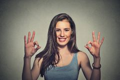 Optimistic woman giving ok sign gesture with two hands. Excited happy young optimistic woman giving ok sign gesture with two hands isolated on gray wall Stock Photography