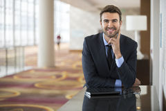Optimistic Young Executive Before Meeting. Handsome optimistic young business man portrait at hotel conference traveling for work meeting Royalty Free Stock Photo