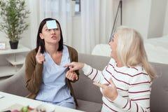 Optimistische ältere Frau und Pflegekraft, die Spaß hat stockbilder