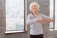 Optimistische Alternfrau, die an der Tanzstunde tangoing ist Stockfotos
