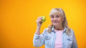 Optimistische bejaarde dame die verse groene appel, gezonde tanden, de stomatologie bijten stock videobeelden