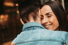 Optimistische Frau, die jungen Mann während der Freizeit umarmt lizenzfreie stockbilder