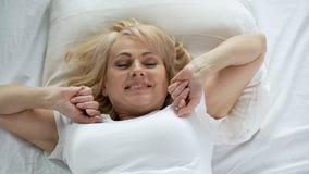 Optimistische Frau von mittlerem Alter, die früh am Morgen, an der Vitalität und an der Energie aufwacht stockfotografie