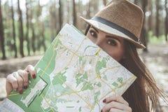 Optimistische junge Frau hält Karte nahe Gesicht stockfotografie