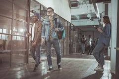 Optimistische junge Männer stehen im Büro stockfotos