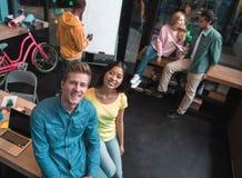 Optimistische junge Mitarbeiter arbeiten im Büro stockfotografie