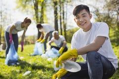 Optimistische mannelijke vrijwilliger die draagstoel verzamelen stock afbeeldingen