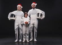 Optimistische Paare von Astronauten mit ihrem Kind drücken Glück aus stockbilder