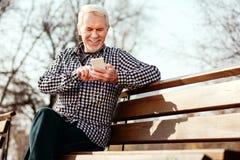 Optimistischer älterer Mann, der über Titelliste entscheidet lizenzfreies stockfoto