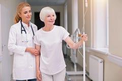 Optimistischer heller Doktor, der ihren Patienten für einen Weg nimmt lizenzfreie stockfotografie